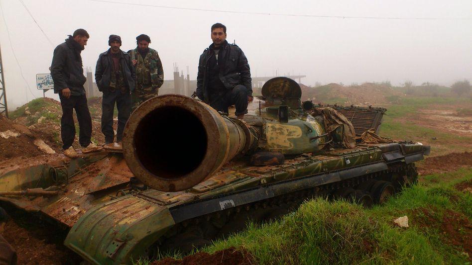Syrische Rebellen auf zerstörtem Panzer: Seit zwei Jahren wüten die Gefechte