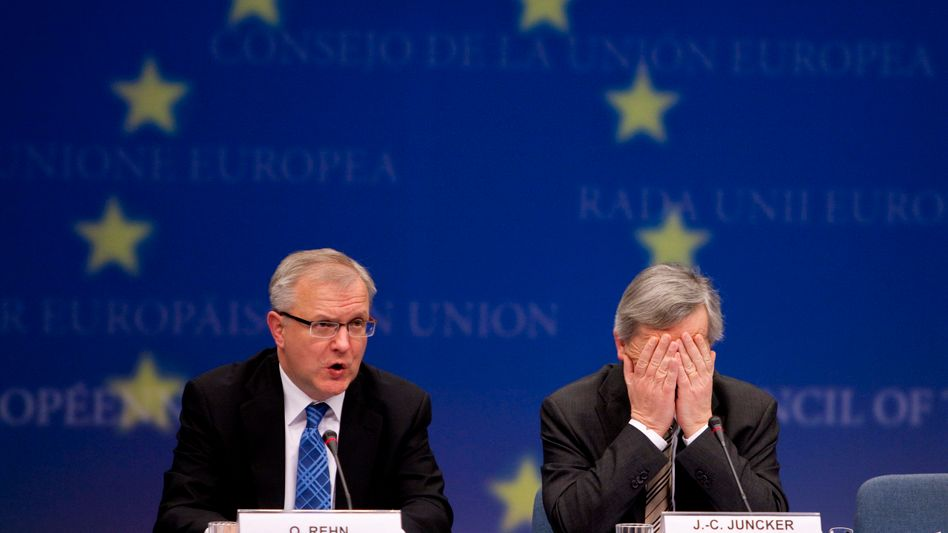 European Monetary Affairs Commissioner Olli Rehn and Euro Group President Jean-Claude Juncker at a news conference in Brussels on Monday