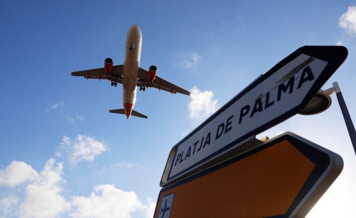 Ein Flugzeug überfliegt bei der Landung auf Mallorca ein Schild, das die Richtung nach Playa de Palma anzeigt