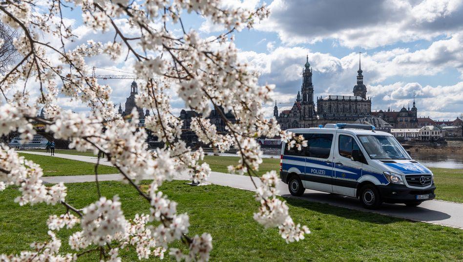 Vor der historischen Altstadtkulisse in Dresden herrscht Leere, nur die Polizei fährt Streife