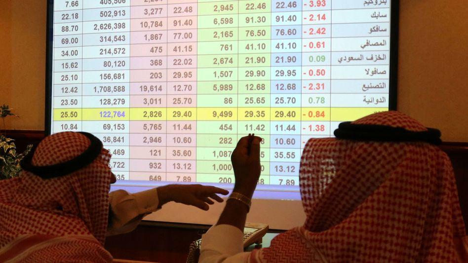 Saudi-arabische Geschäftsleute studieren Aktienkurse auf dem Bildschirm einer Bank