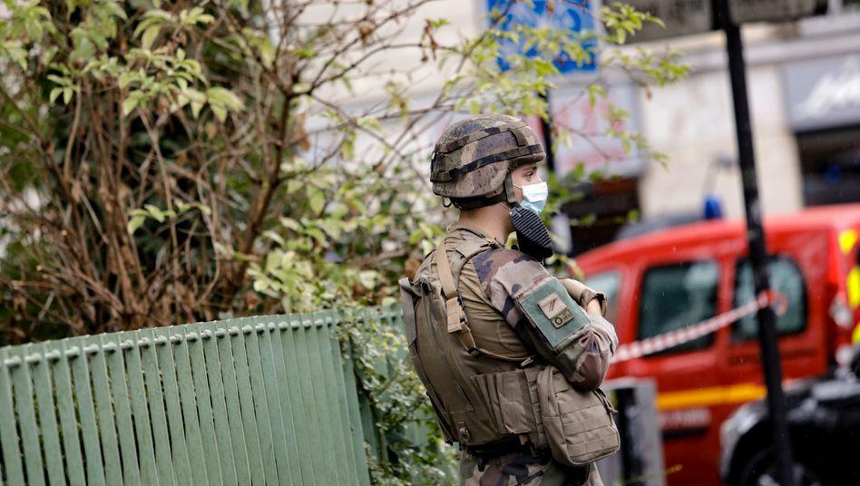 Mit Maske und Waffe: Ein französischer Soldat am Tatort in Paris