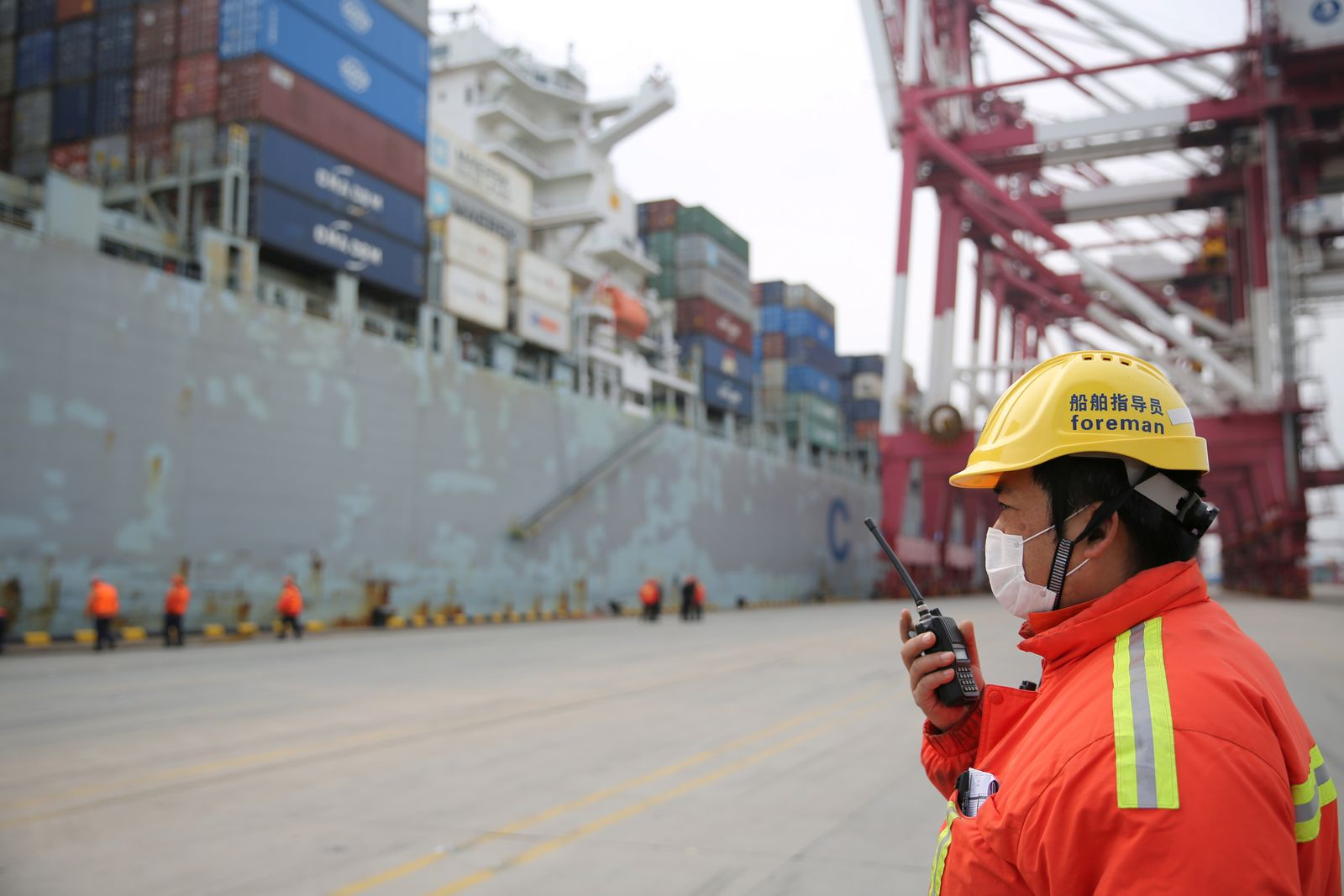 Foreman wearing a face mask works as a cargo ship docks at a container terminal of Qingdao port