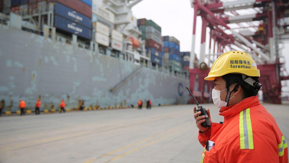 Ein Vorarbeiter steht neben einem Containerschiff im Hafen von Qingdao im Nordosten Chinas