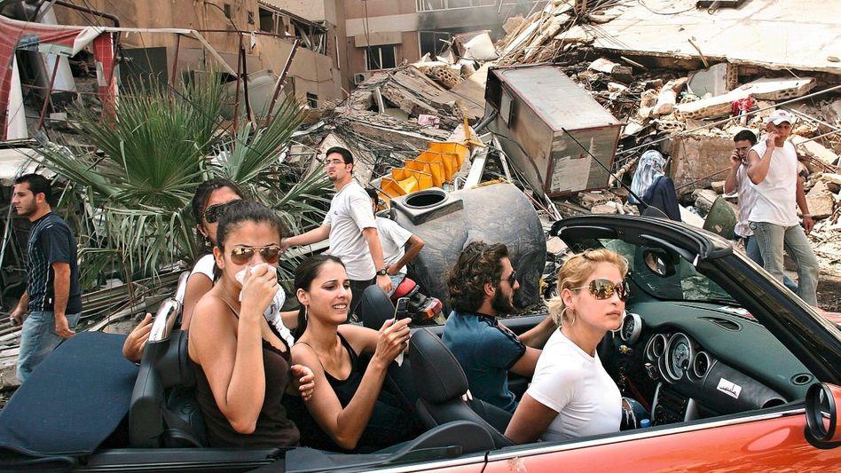 Reiche junge Libanesen besichtigen im August 2006 ein durch israelische Angriffe zerstörtes Viertel von Beirut.