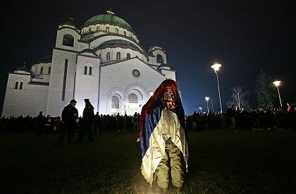 A Serb child wrapped in a Serbian flag during an Orthodox service on Monday in Belgrade.