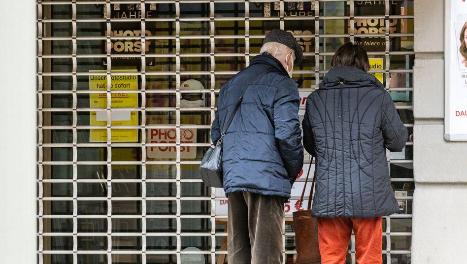 Passanten stehen vor einem geschlossenen Geschäft
