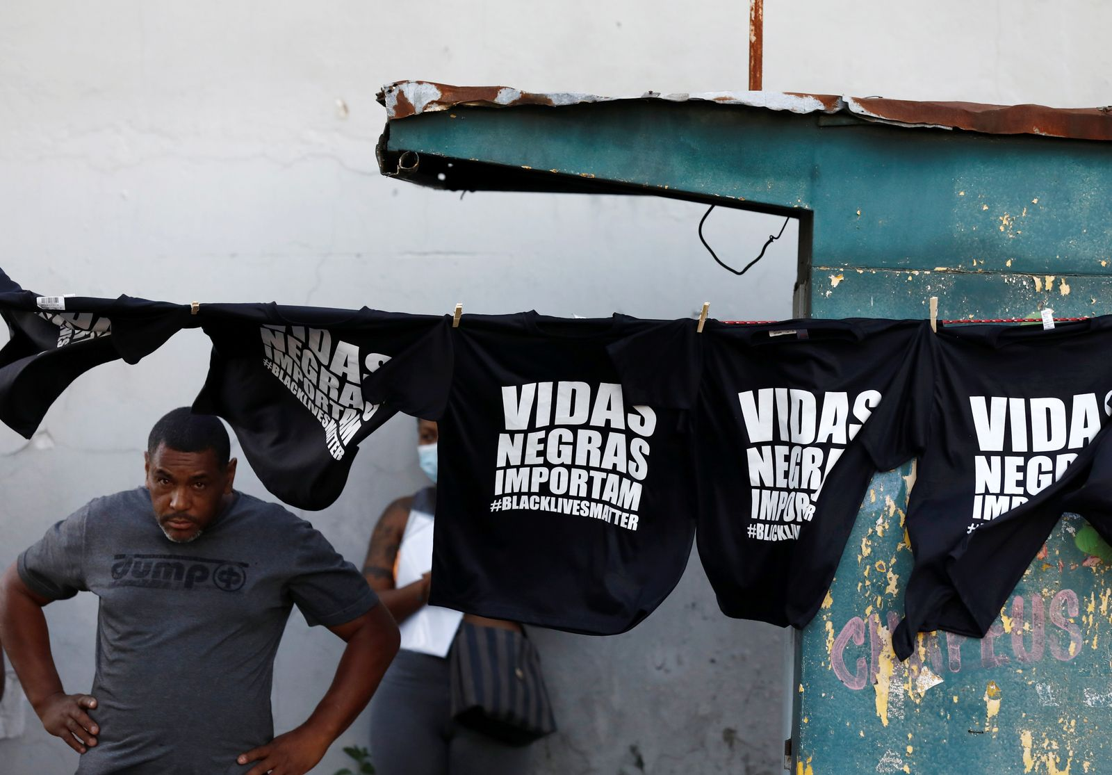 "Man stands next T-shirts that's read:""Black Lives Matter"" during a protest against racism, after Joao Alberto Silveira Freitas was beaten to death by security guards at a Carrefour supermarket in Porto Alegre"