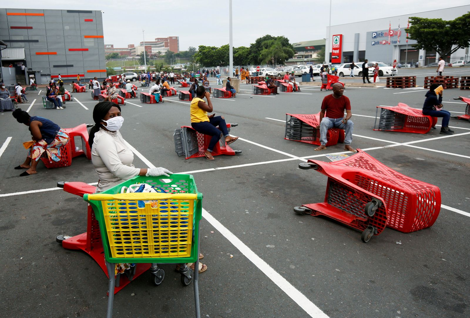 Shoppers queue at a grocery store during a nationwide 21 day lockdown in an attempt to contain the coronavirus disease (COVID-19) outbreak in Chatsworth near Durban