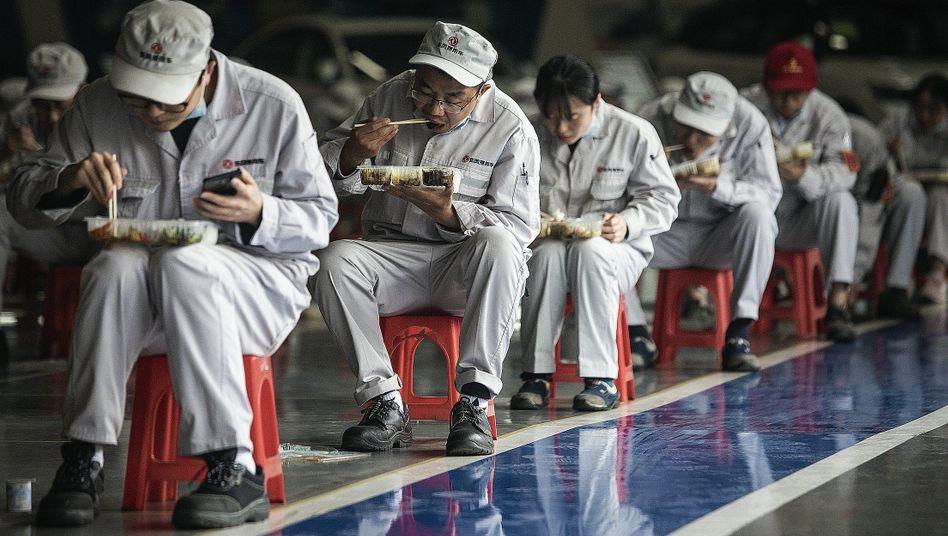 Angestellte in einer Fabrik in Wuhan beim Mittagessen mit Sicherheitsabstand