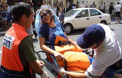 Sanitäter kümmern sich am Ort des Attentats um eine verletzte Israelin
