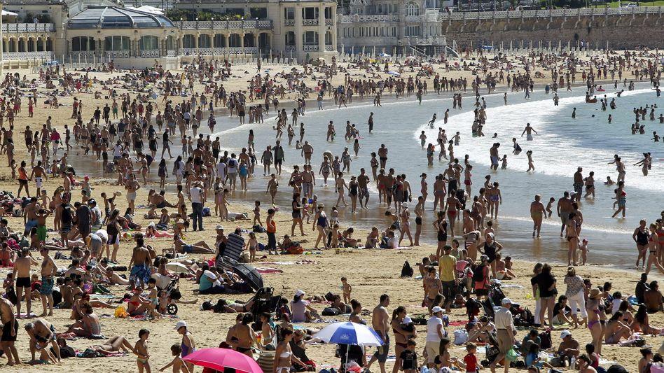 Urlauber am Strand in Spanien: Bei Unfall oder Krankheit kann es teuer werden