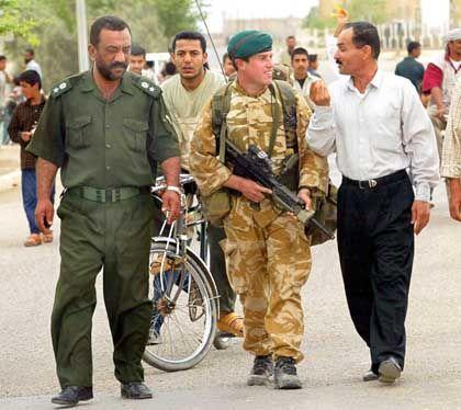 Basra: Ein britischer Soldat und ein irakischer Polzist im Gespräch mit einem Zivilisten