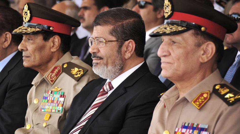 Präsident Mursi (Mitte) und Feldmarschall Tantawi (l.): Konfrontationskurs in Ägypten