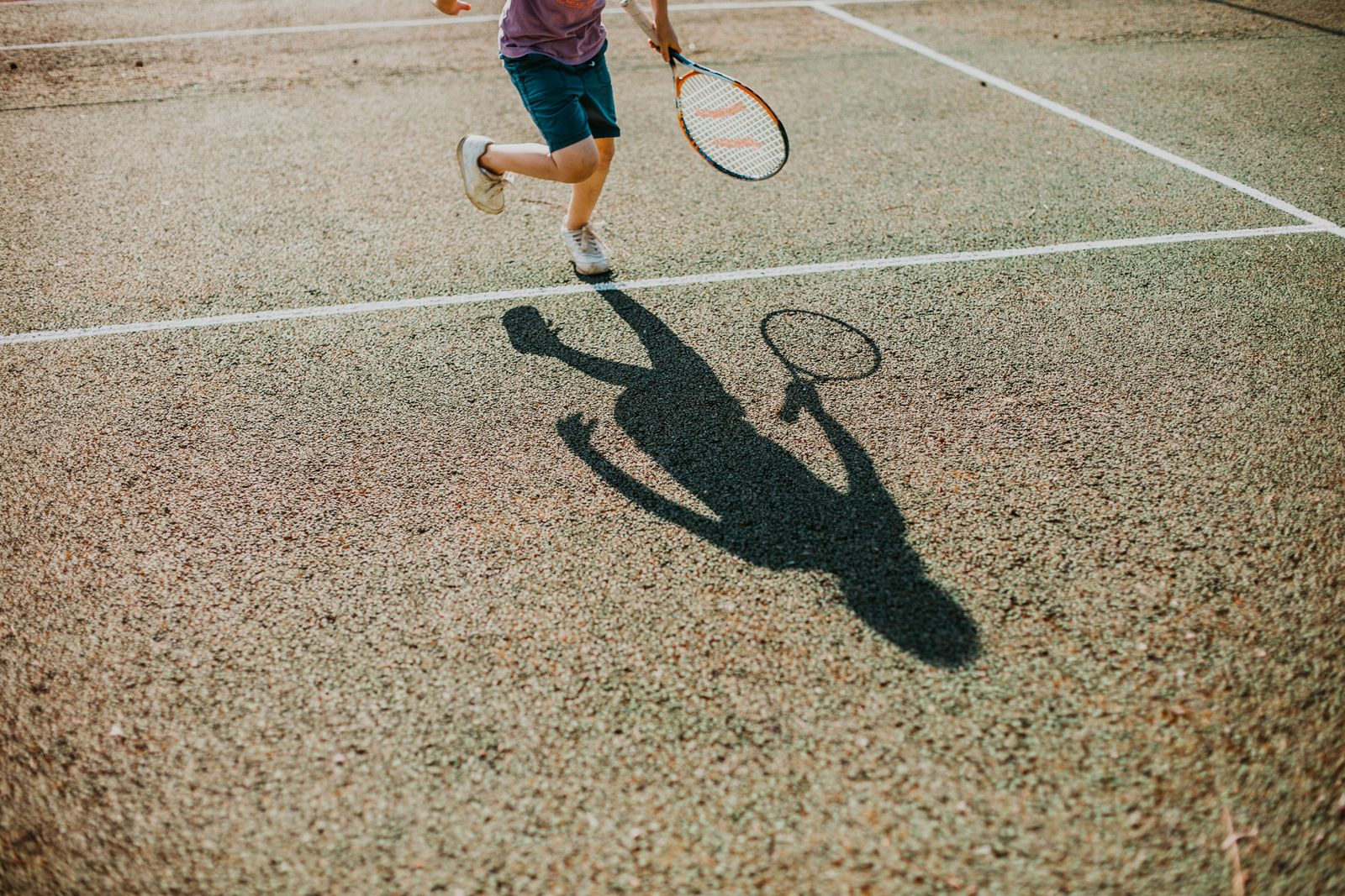 low section of boy playing tennis in sunny day