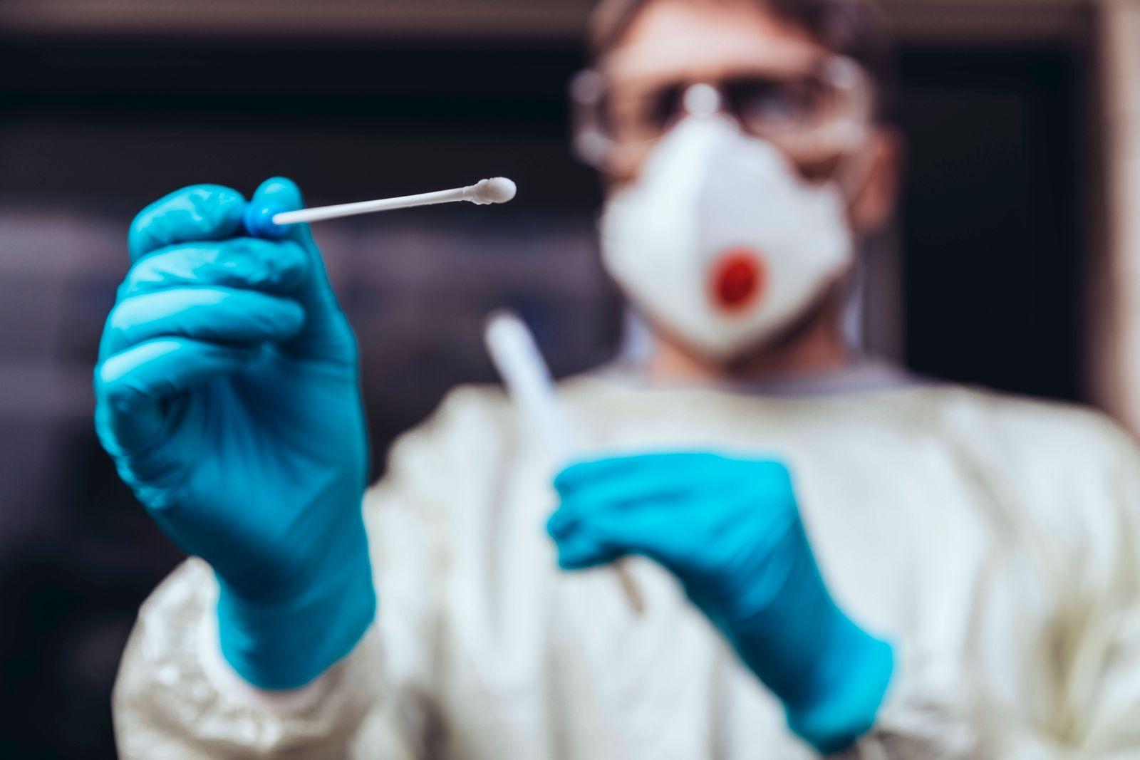 Healthcare worker holding swab test kit for PCR testing model released Symbolfoto MFF05400