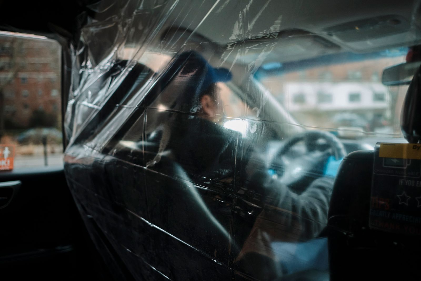 A cab driver uses plastic to shield himself from the coronavirus, in New York, March 16, 2020. (John Taggart/The New York Times)