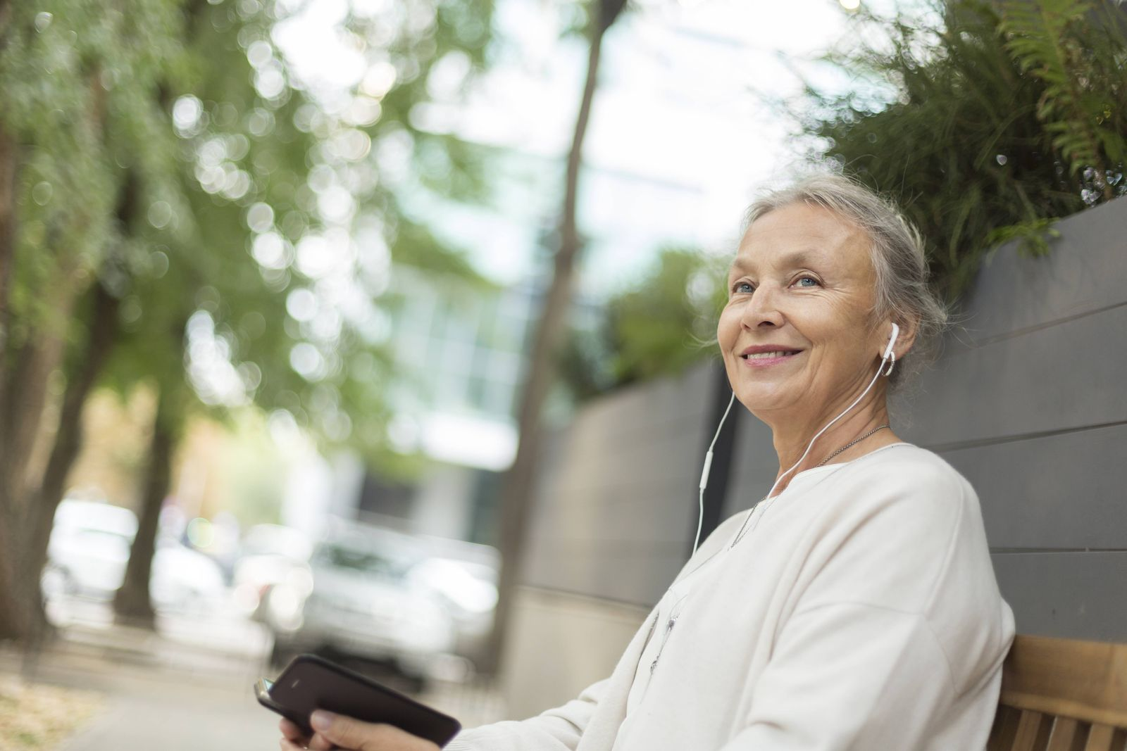 Smiling senior woman sitting on a bench outdoors with cell phone and earphones model released Symbol