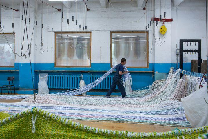 Einer der wenigen Männer in der Werkhalle zieht Seile in Position