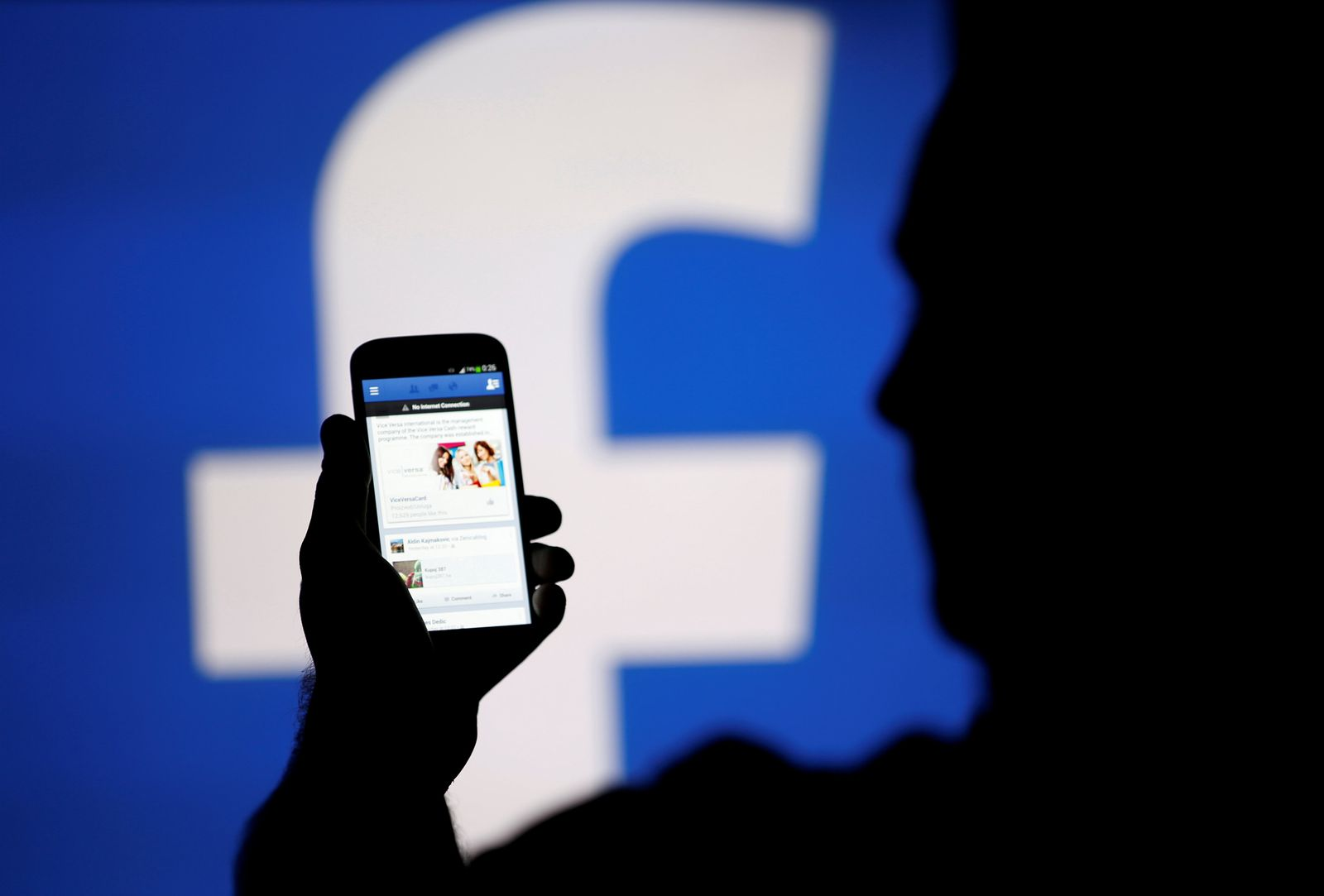 FILE PHOTO: A man is silhouetted against a video screen with an Facebook logo as he poses with an Samsung S4 smartphone in this photo illustration taken in the central Bosnian town of Zenica