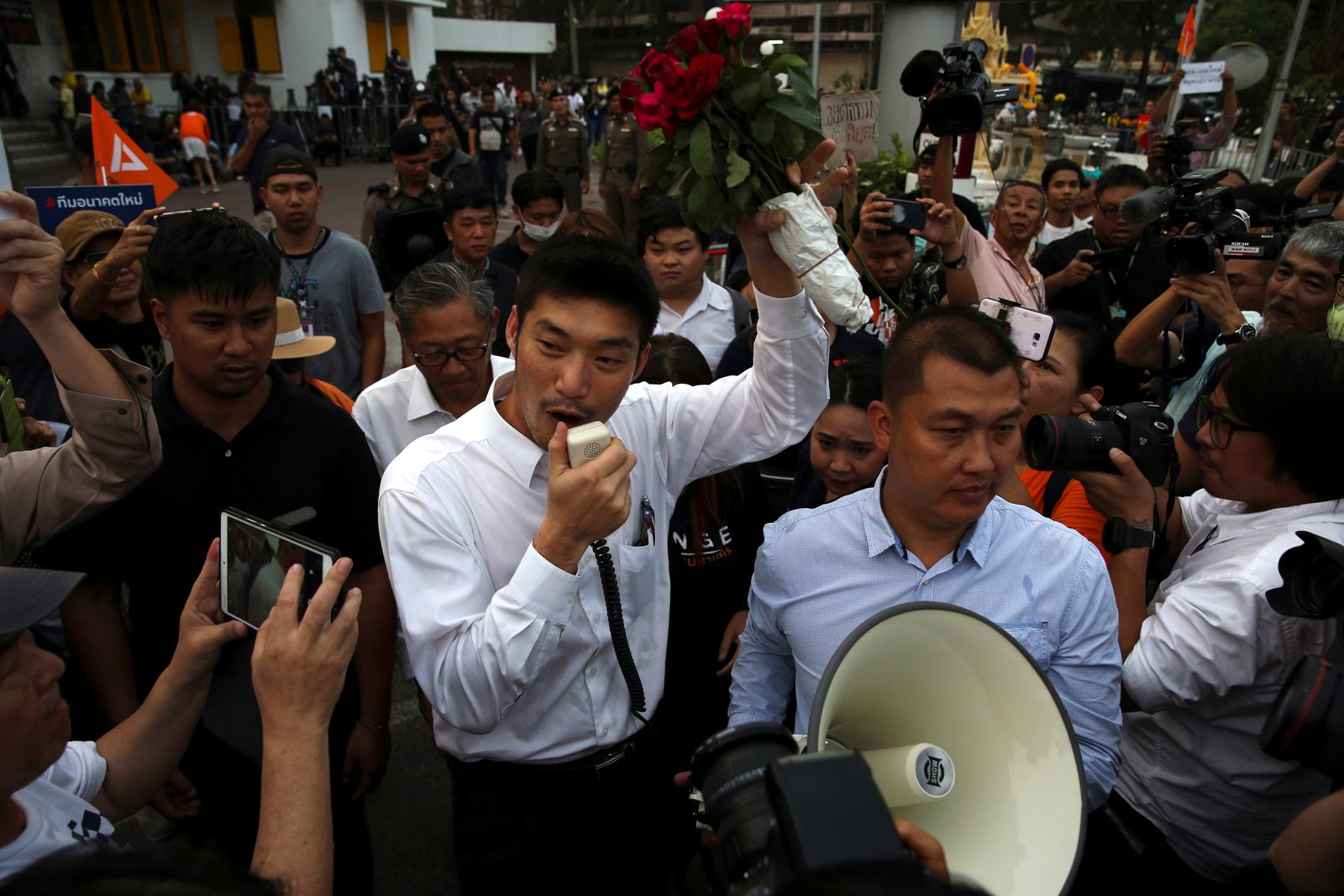 Thailand's opposition Future Forward Party leader Thanathorn speaks to his supporters as he leaves after reporting to a Bangkok police station