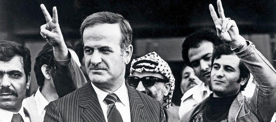 Syriens Präsident Hafis al-Assad (mit PLO-Chef Jassir Arafat, mit Sonnenbrille) auf einem arabischen Gipfeltreffen im libyschen Tripolis, April 1980.