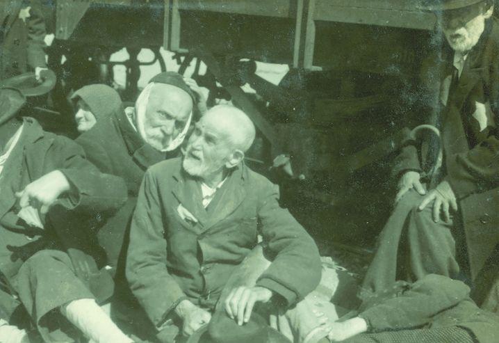 (Foto von Ernst Hofmann oder Bernhard Walter, 26.5.1944 - Foto 100 des Lili Jacob-Albums) Einem Mann war offenbar vor Abfahrt des Zuges sein Bart geschoren worden. Er versuchte die demütigende Blöße mit einem Tuch zu verdecken. Ganz teilnahmslos – zu Tode erschöpft – schaute rechts Lili Jacobs Großvater in die Kamera.
