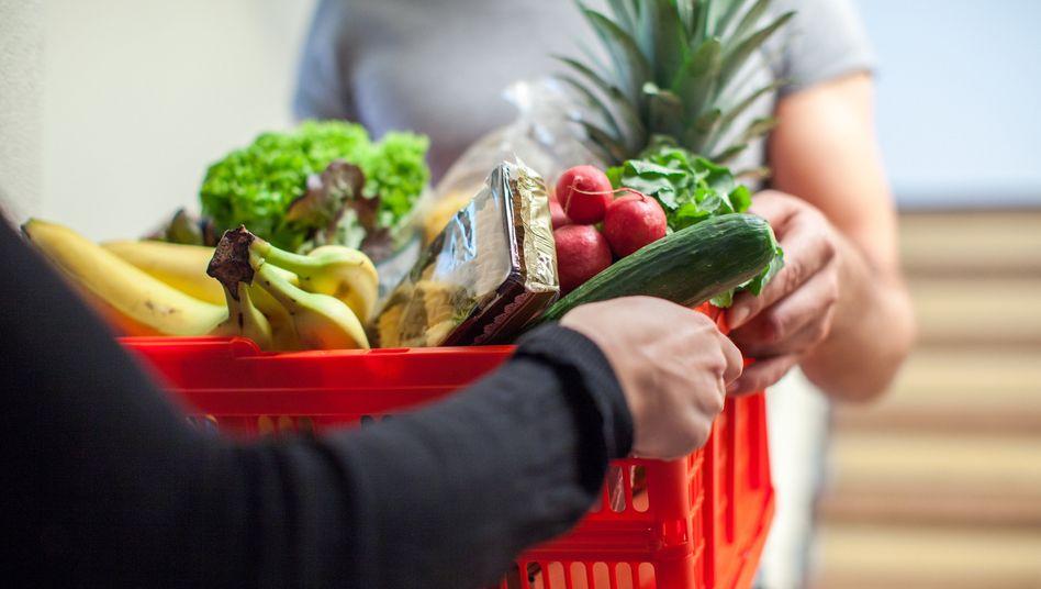 Übergabe von Einkäufen: Vielerorts helfen junge Menschen Älteren beim Einkauf