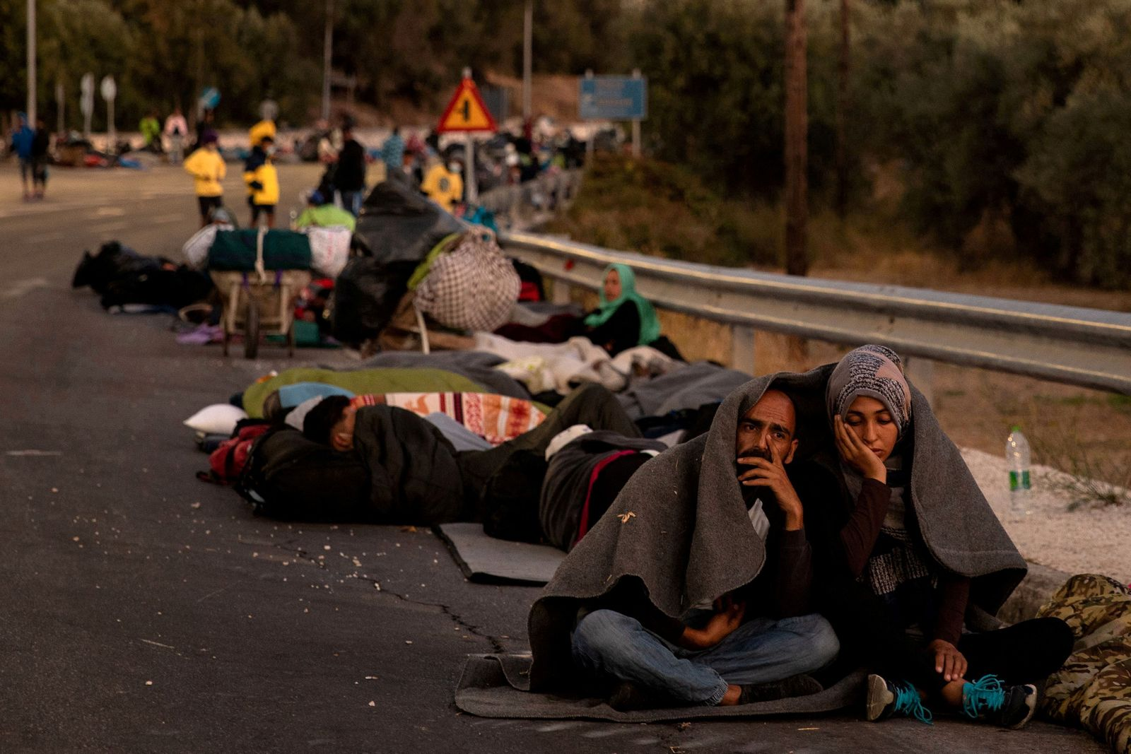 FILE PHOTO: Couple sits covered with a blanket as refugees and migrants camp on a road following a fire at the Moria camp on the island of Lesbos