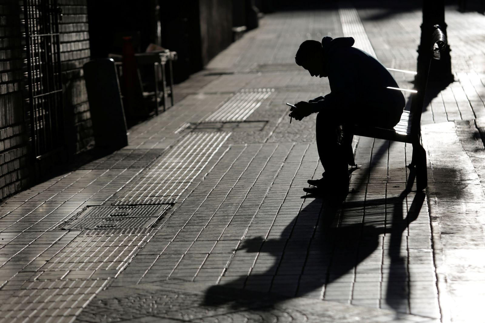 Man checks his phone while sitting on a bench in Saltillo
