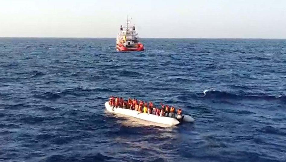 Migranten sitzen in einem kleinen Boot auf dem Mittelmeer (Symbolbild)