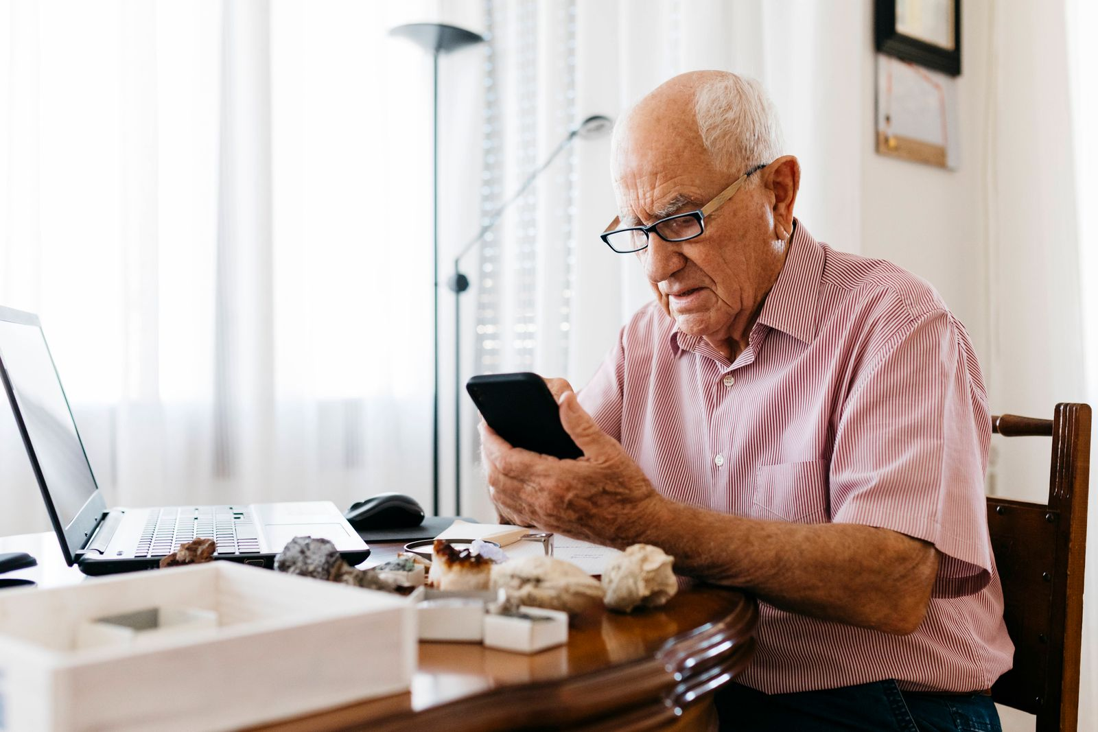 Senior man using smart phone while doing research on mineral and fossil at home model released Symbolfoto property relea