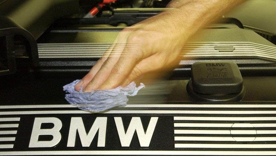 Pflege: Ein Mitarbeiter einer BMW-Niederlassung putzt einen Motorblock