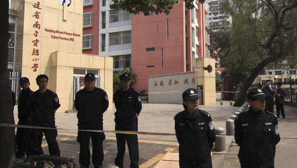 Nach der Bluttat: Polizisten bewachen den Eingang der Grundschule in Nanping