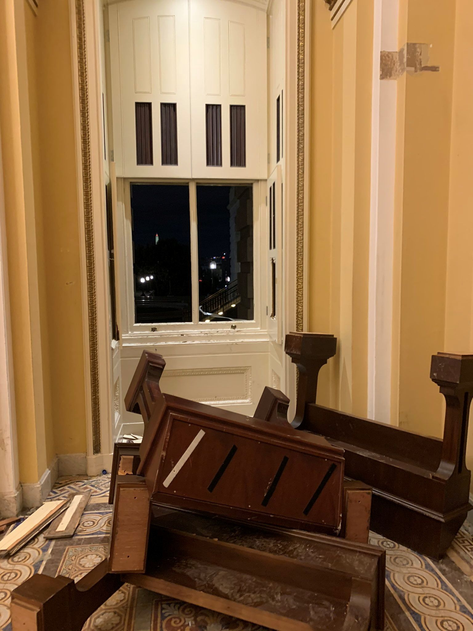 Flipped furniture and a broken window glass lie on the floor inside the U.S. Capitol in Washington