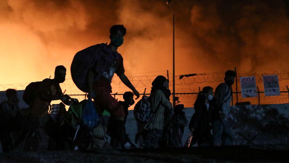 Menschen vor dem brennenden Lager Moria