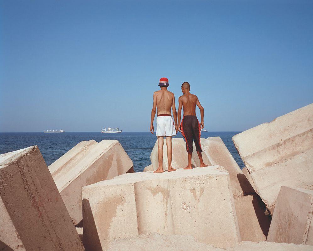 """Die Serie """"Rochers Carrés"""" des Fotografen Kader Attia zeigt junge Menschen, die von dem gleichnamigen Strand in Algerien über das Meer Richtung Europa blicken"""