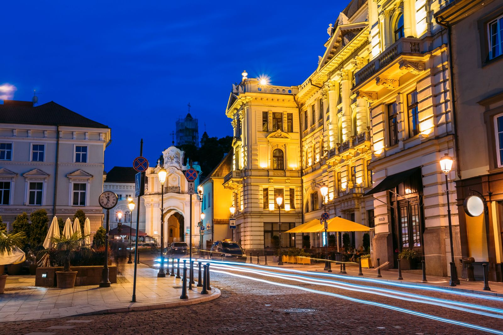 Vilnius Lithuania. Lithuanian National Philharmonic Society Building In Bright Evening Illumination And Basilian Gate On Ausros Vartu Street With Motion Blur Effect On Road In Summer Under Blue Sky. (Ryhor Bruyeu)