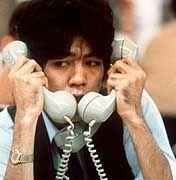 Kann man so noch lauschen? Ein Börsenmakler an der Tokioter Börse mit drei Telefonen
