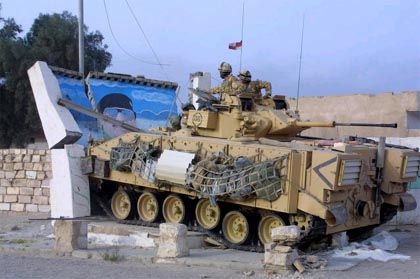"""Ein Panzer der """"Wüstenratten"""" rammt eine Mauer und zerstört ein Heldenbild von Saddam Hussein."""
