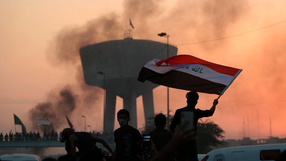 Eine Gruppe Demonstranten schwenkt die irakische Nationalflagge