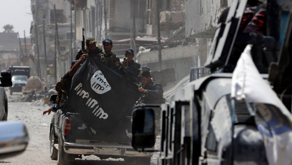 Sicherheitskräfte mit IS-Flagge im Irak (Archivbild)