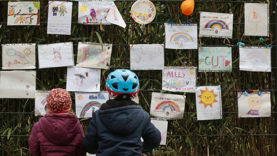 Zwei Kinder vor einer Grundschule in Düsseldorf, die während der Pandemie Nachrichten gegen die Coronakrise aufgehängt hat (Archivbild)