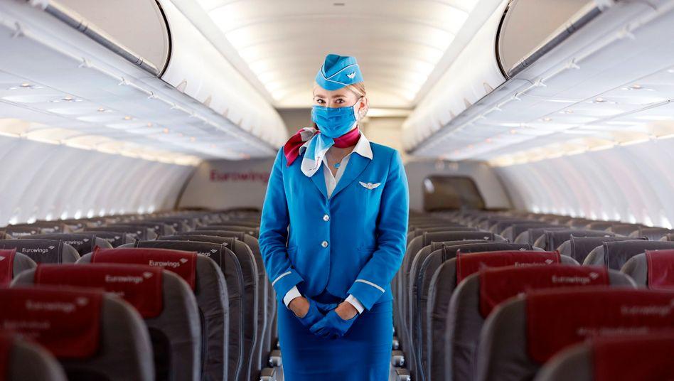 Eine Stewardess mit Mund-Nasen-Schutz in einer Eurowings-Maschine