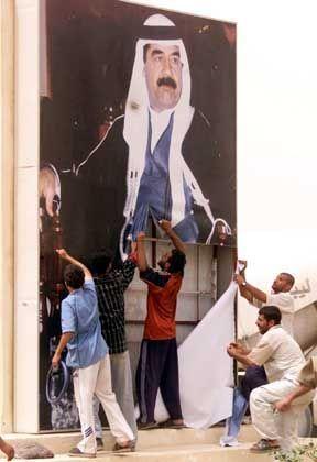 Iraker reißen ein Plakat Saddam Husseins herunter