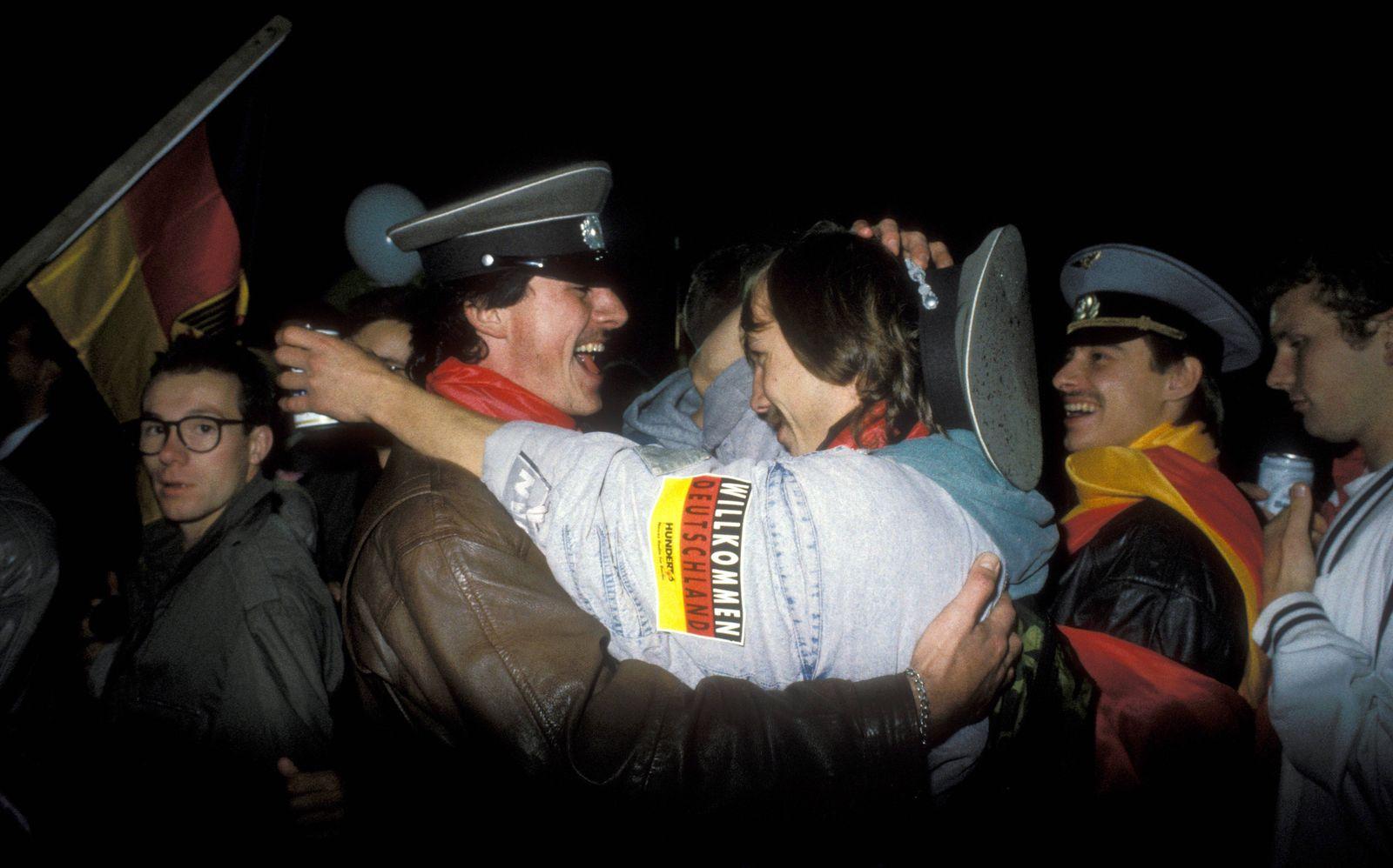 POLITIK 25 Jahre Deutsche Einheit: Die Wiedervereinigung Männer umarmen mit sich Mützen der NVA während der Feierlichke