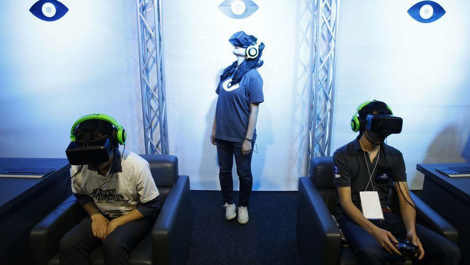Messebesucher probieren Prototypen der Oculus Rift aus