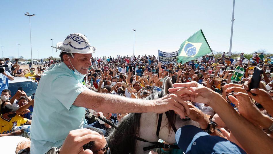 Jair Bolsonaro bei einem Auftritt am vergangenen Donnerstag: Maske unter dem Kinn, Hände in der Menge