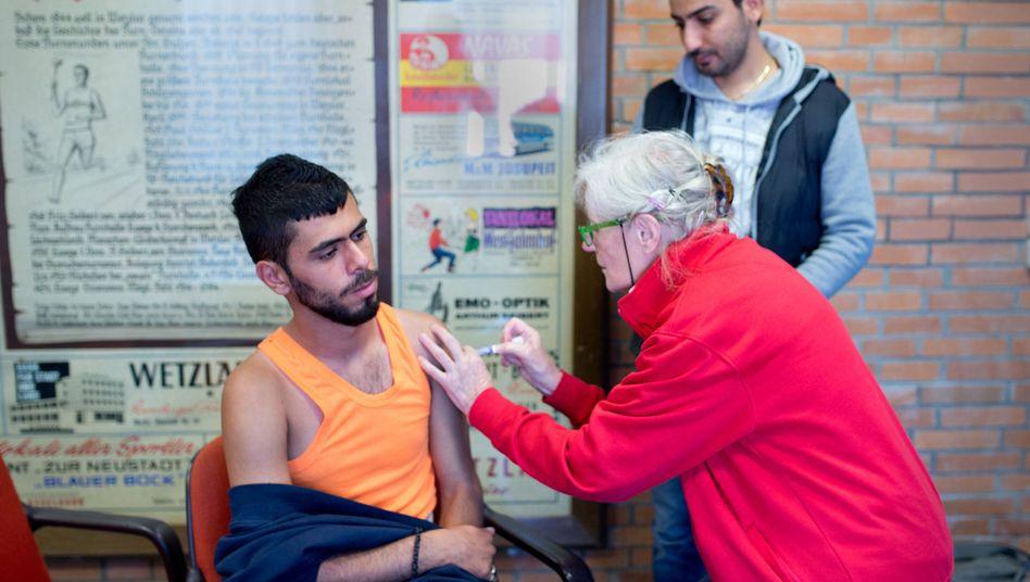 Eine Ärztin impft einen Syrer in Wetzlar