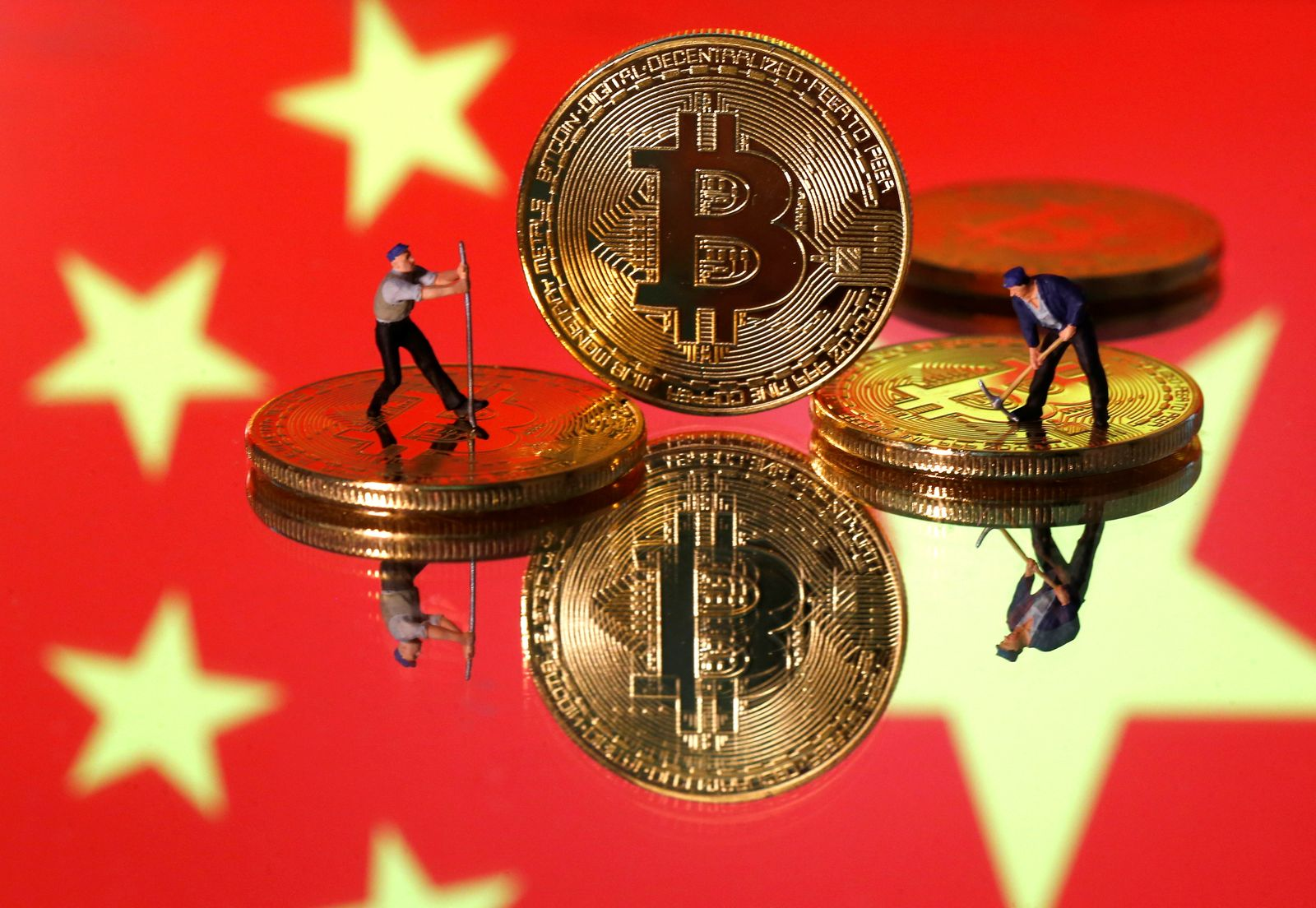 FILE PHOTO: Picture illustration of small toy figurines and representations of the Bitcoin virtual currency displayed in front of an image of China's flag